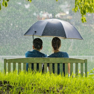 Romantic-couple-sitting-in-park-while-raining-600x375
